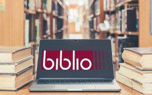 Notebook screen open in a library among old stacks of books. On the screen there is the biblio project logo
